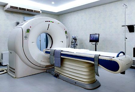 Doctors analyzing X-ray with patient lying on MRI scan machine in hospital